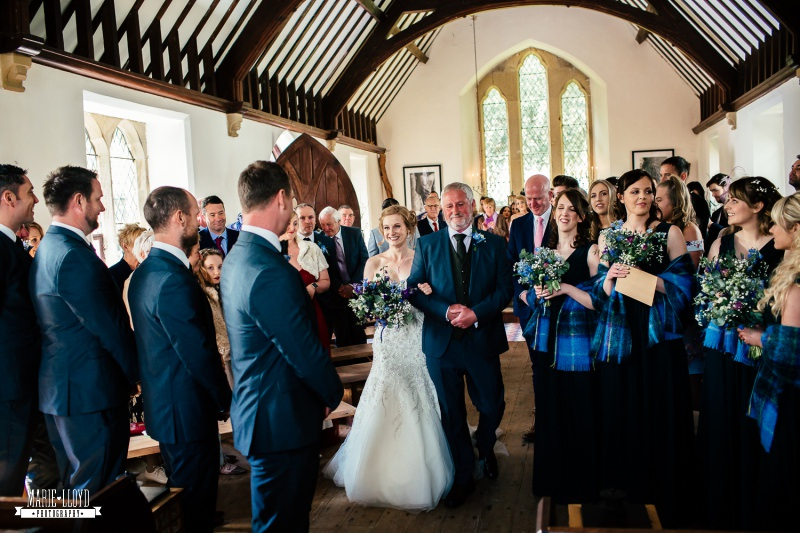 father of the bride and bride walk down the aisle