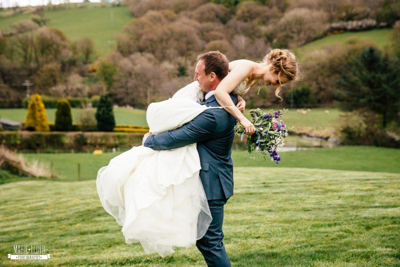 groom holding bride over his shoulder