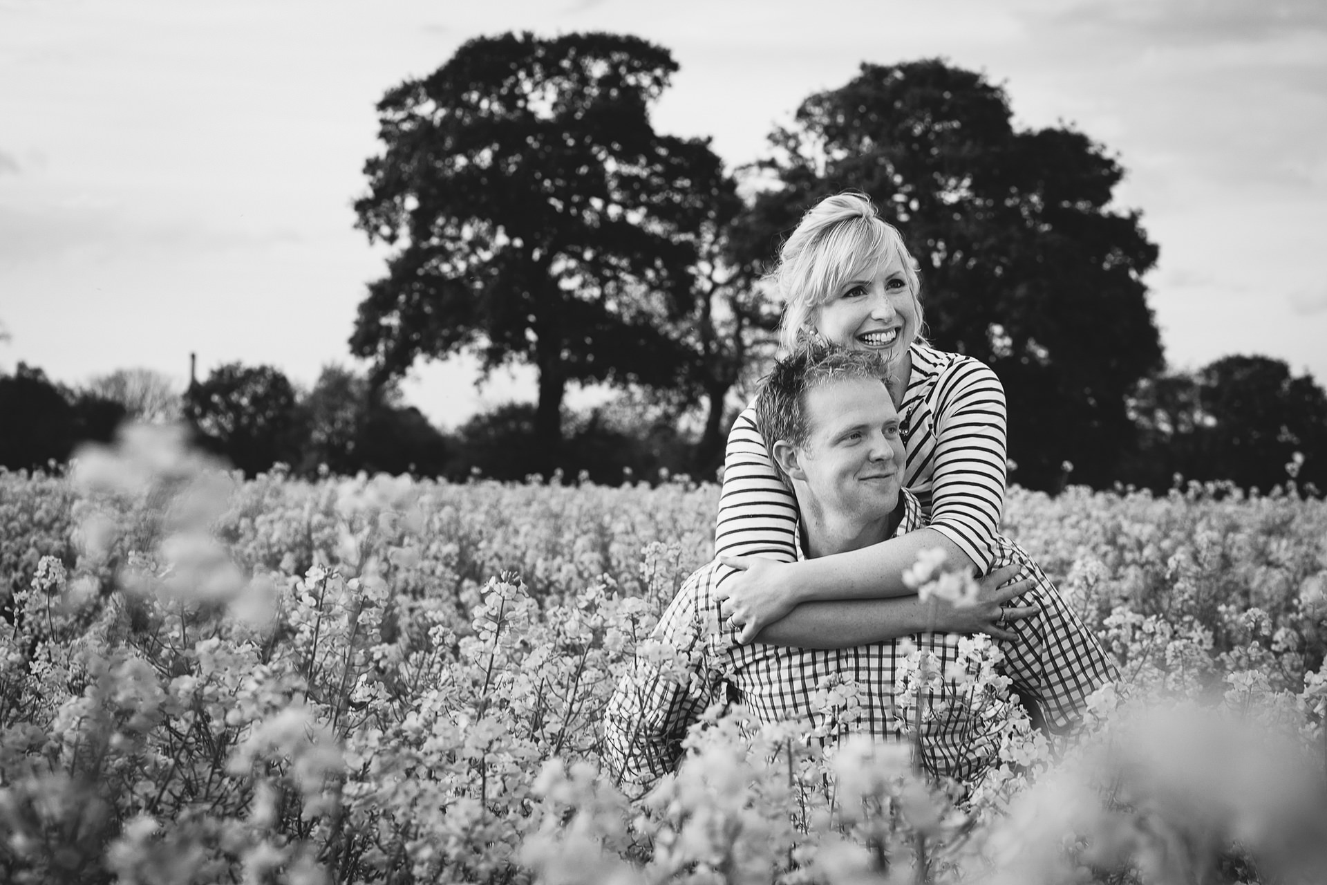 Engagement shoot of couple having a piggy bank in a field of rapseed