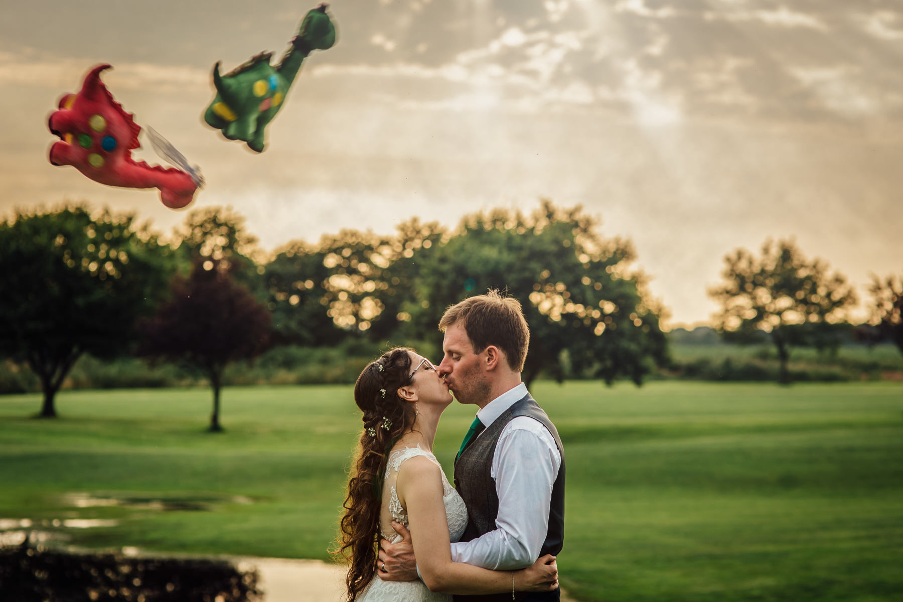 Couple kissing with two toy dragons being thrown
