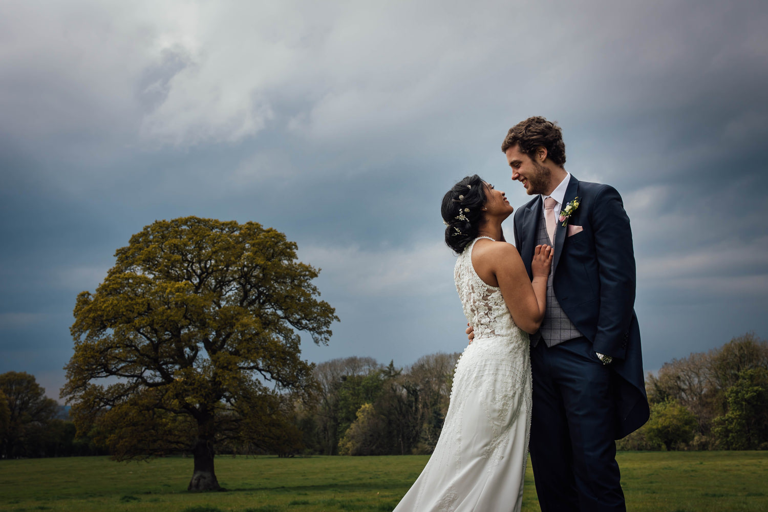 newly married couple hugging beside a tree in Pentre Mawrs gardens.