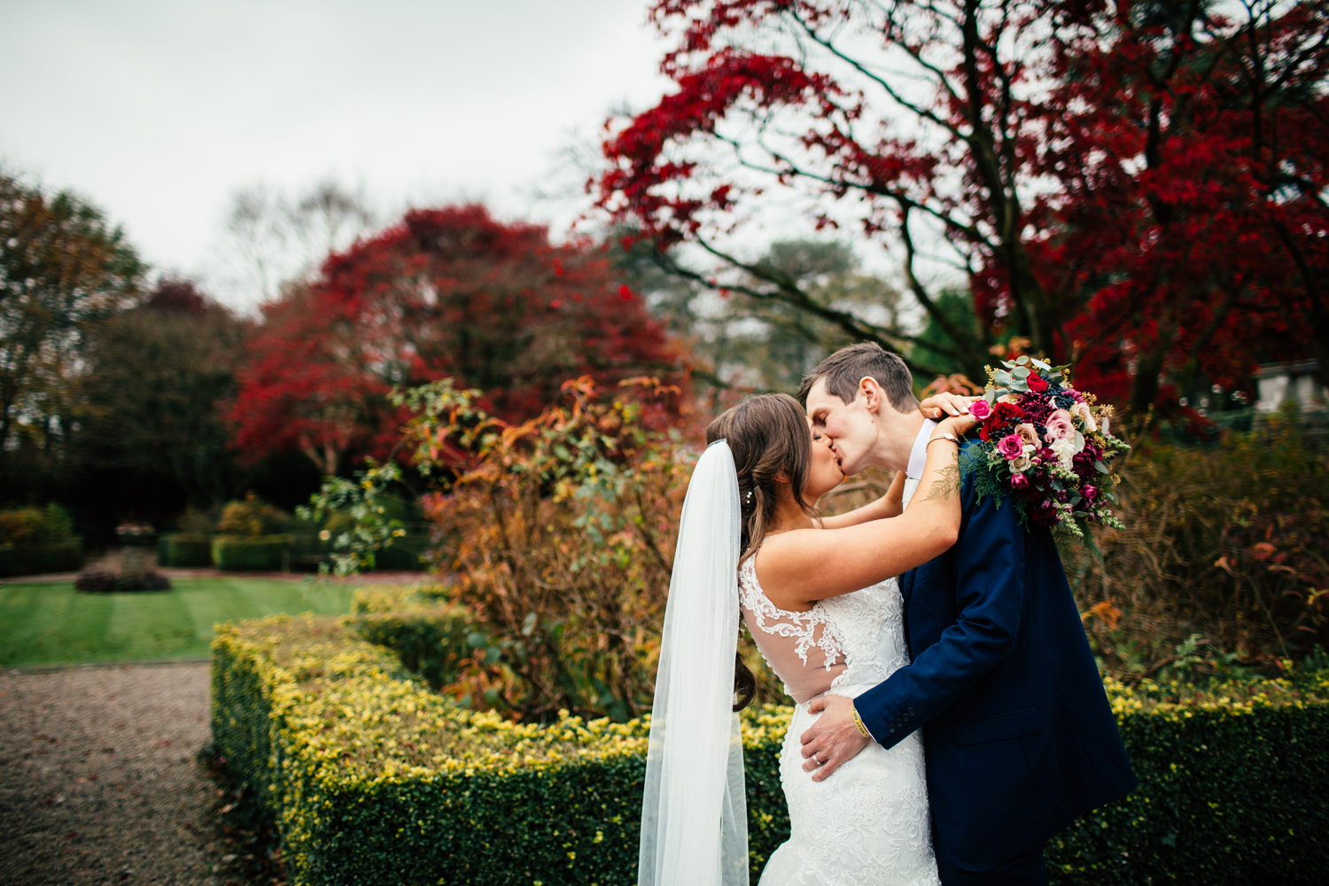 Newly married couple kissing in gardens at Eaves Hall