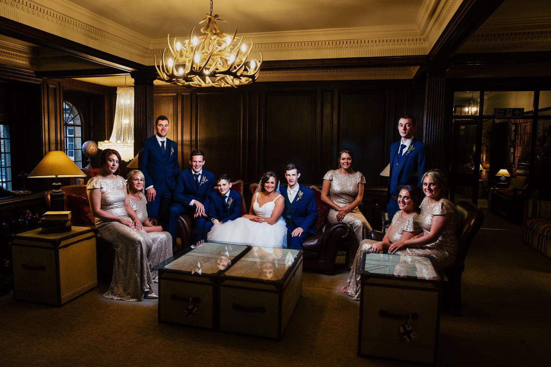 Creative bridal party group shot indoors at Eaves Hall